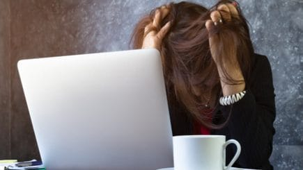 Woman sitting at her laptop with her head in her hands and her hair over her face.