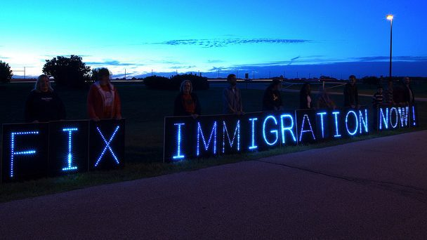 """Lit up letters spelling """"Fix Immigration now"""" against a dark blue sky with people standing behind the letters."""