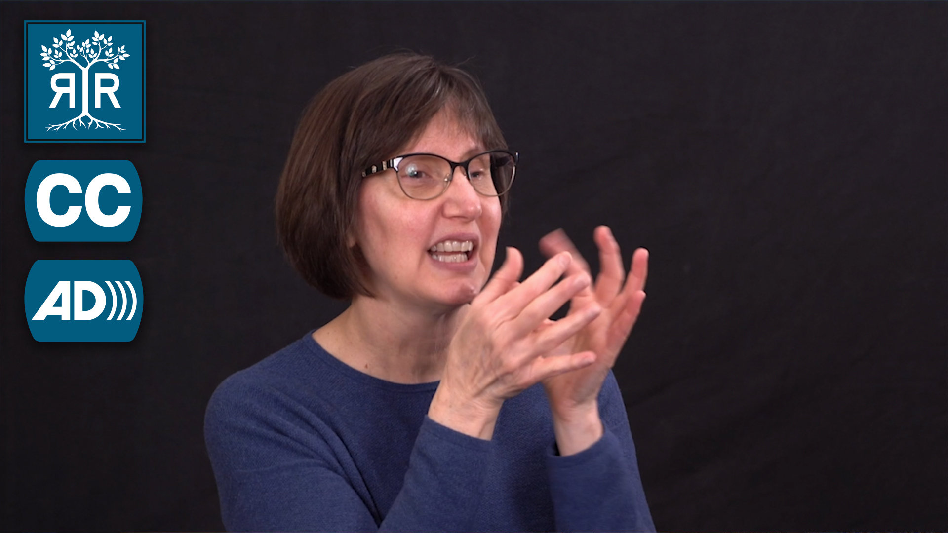Debra, a white woman with short brown hair and glasses, signs to camera.