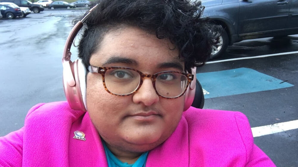 Photo of the author wearing pink headphones and a hot pink jacket.