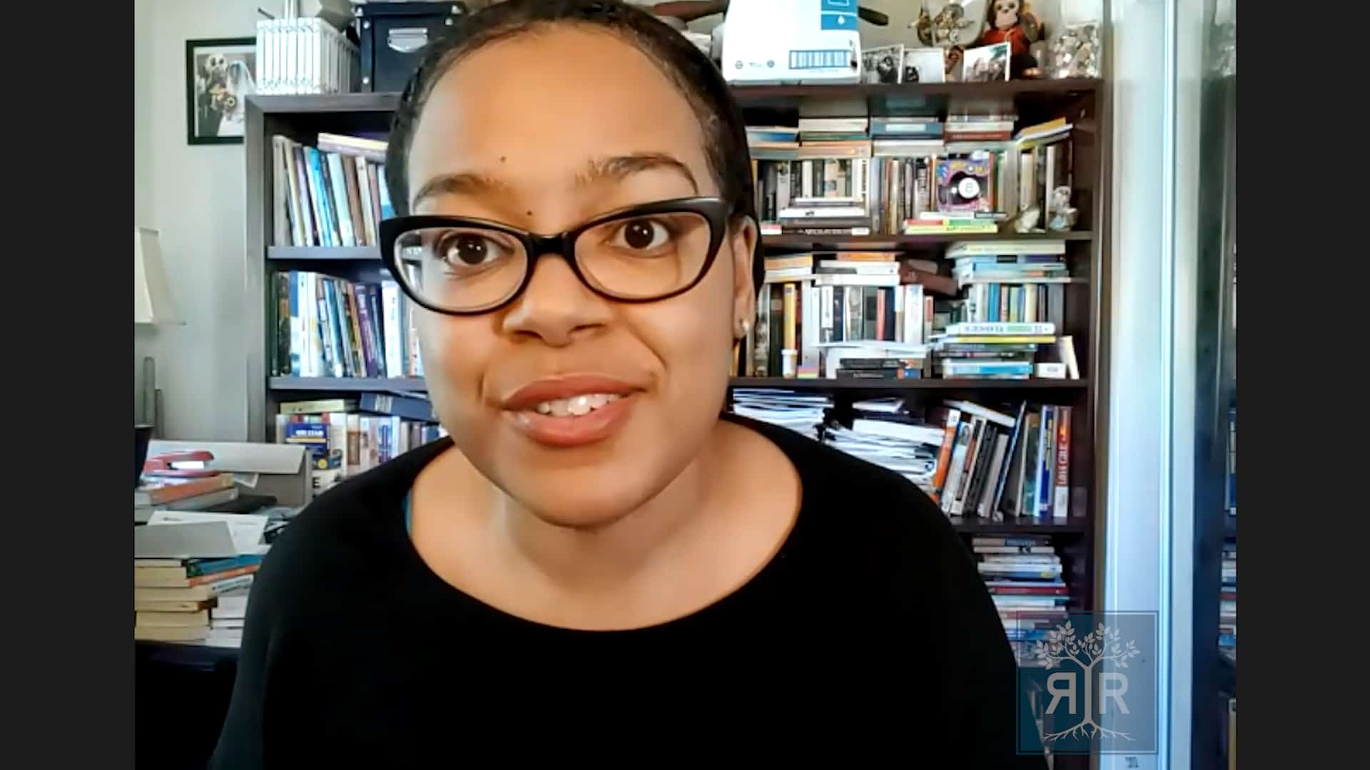 Young POC Femme with black glasses.