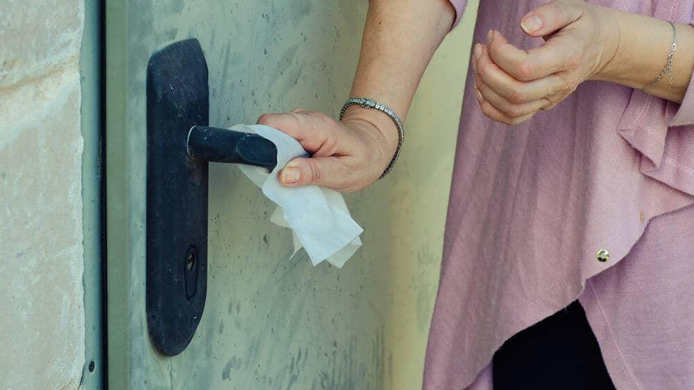 A person grabs a door handle using a napkin
