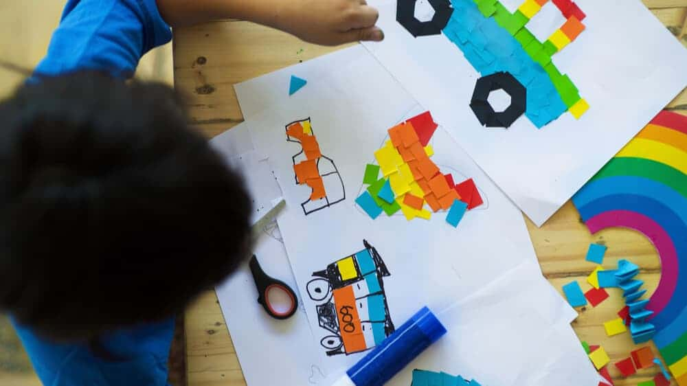 A photo taken from above of a kid doing crafts, making rainbows and drawing trucks.