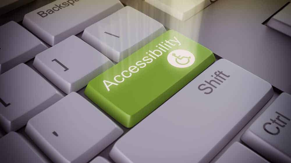 """Computer keyboard with a big green key that says """"accessibility"""" and has a small access symbol. There's a spotlight shining on the accessibility key."""