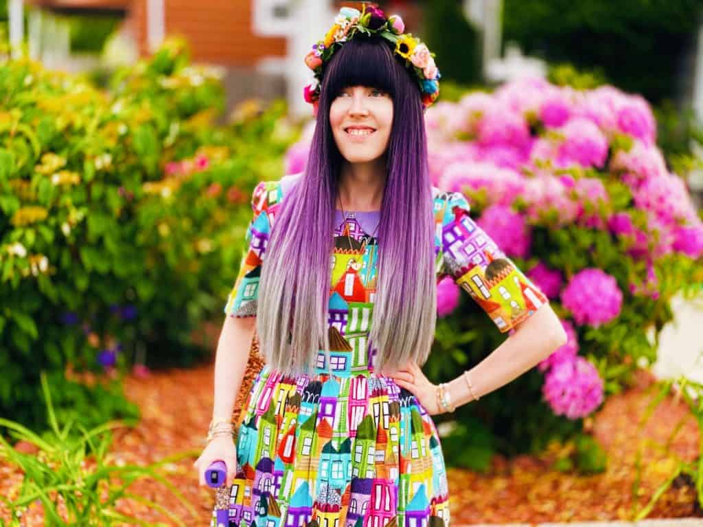 Alaina, a white nonbinary person with long hair that is dark brown fading into lavender and gray, stands outside in front of a colorful garden of flowers. Alaina is wearing a rainbow flower crown on her head and a dress with a colorful houses pattern on it. She has one hand on her hip and another hand on a lavender cane. Alaina has blue eyes that are looking into the distance.