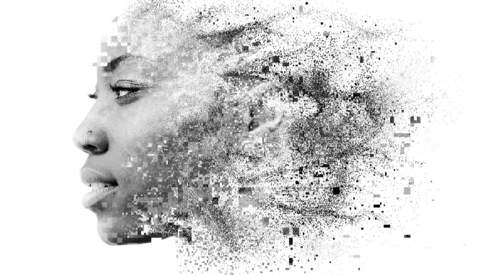 A greyscale photo of a Black woman's face fades into swirls of pixels.