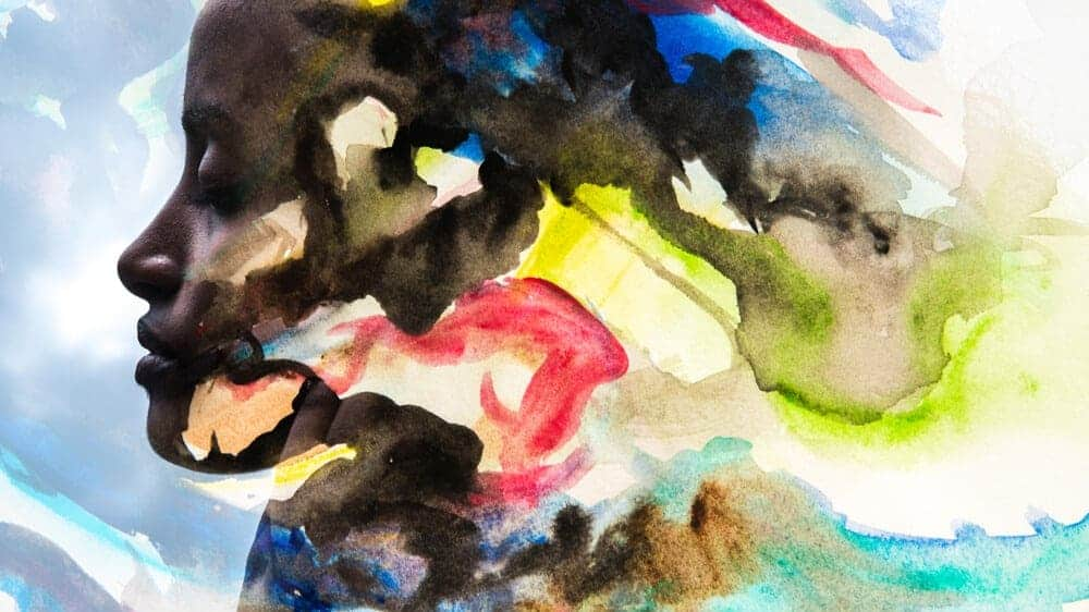 A Black woman with closed eyes fades into a swirl of painted rainbow colors