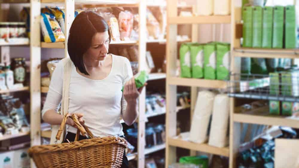 Woman in a grocery store holding a basket in one hand and a product in the other hand, reading its label.