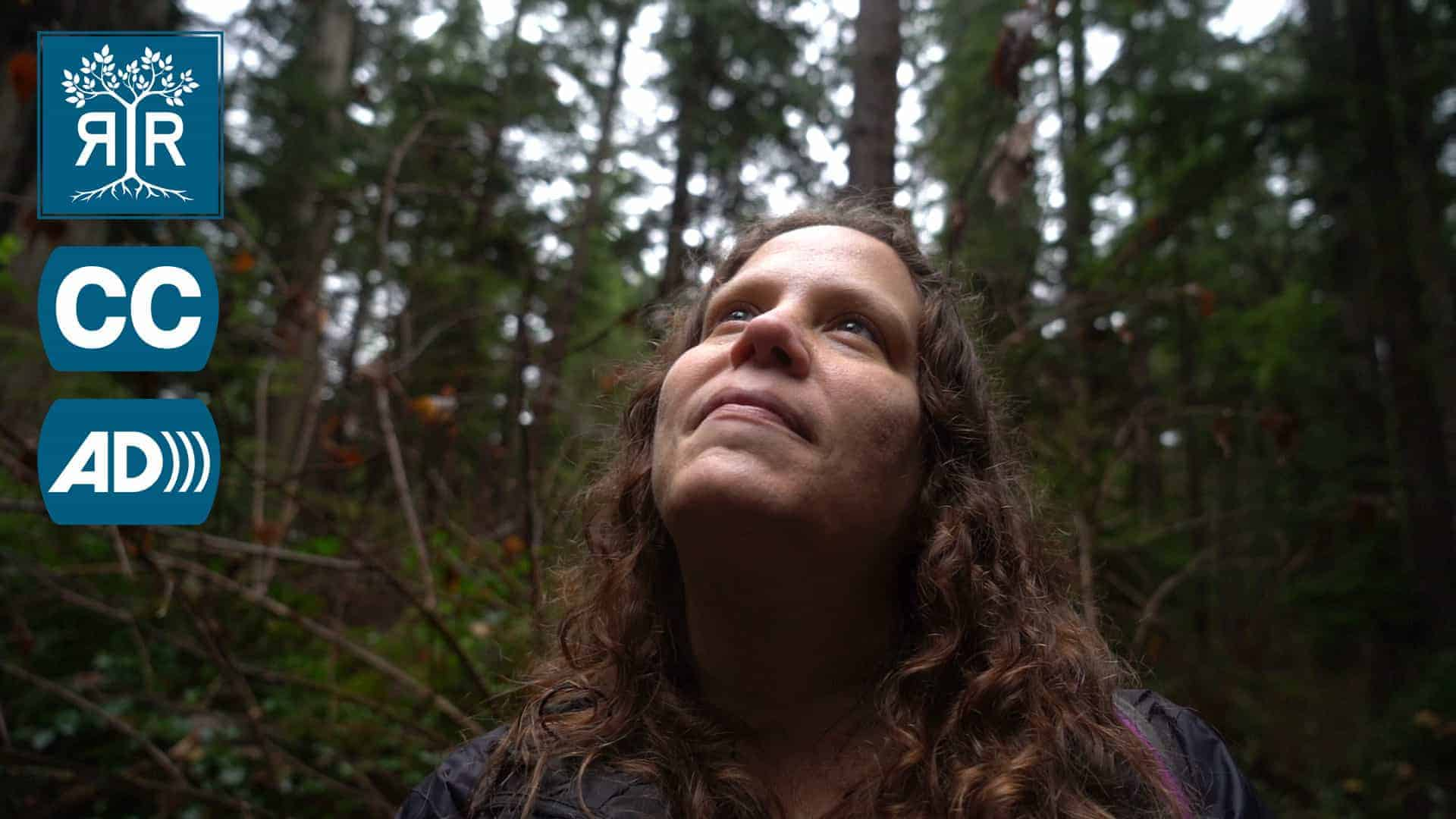 A White person with brown wavy hair looks up towards the sky in a forest. There is a Rooted in Rights icon, a Closed Captioning icon, and an Audio Description icon on the left of the image.