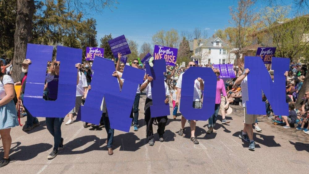 "A group of people marching down a street, holding big purple letters that spell ""union."""