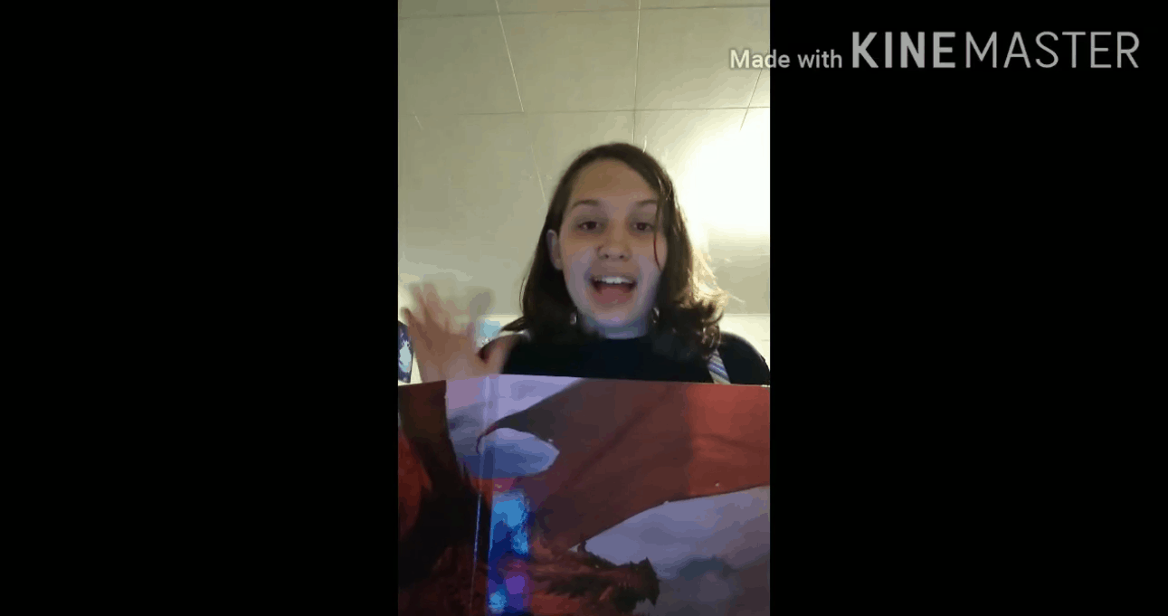 Alexis waves to camera from behind a Dungeons and Dragons folder.