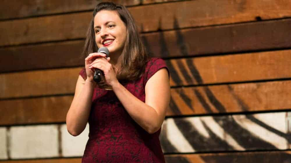 Photo of Nina G, a white woman with straight shoulder length brown hair, wearing a red dress and speaking into a microphone.