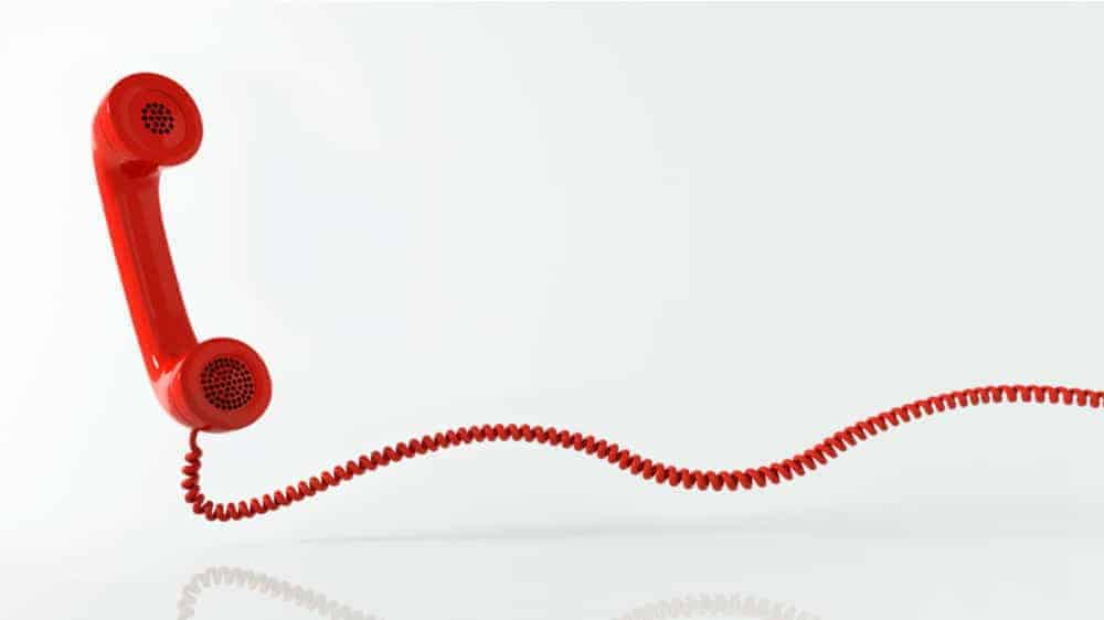 A red telephone receiver with a long red wire