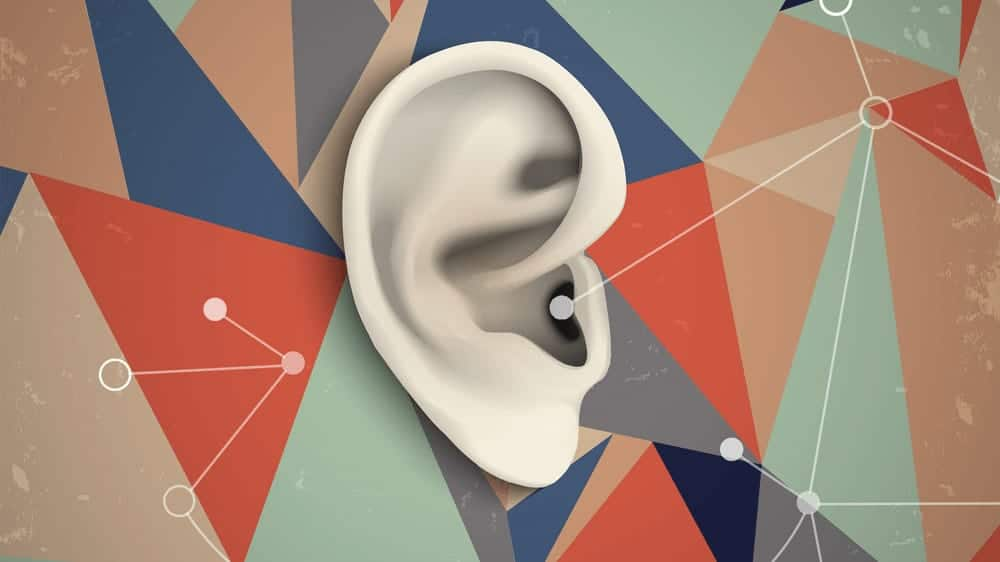 Image of an ear surrounded by geometric multicolored triangles.