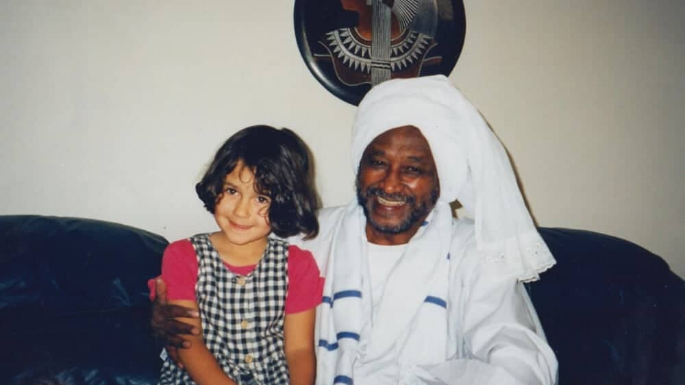 The author as a young child sitting on the lap of her Sudanese grandfather, who is dressed in a traditional white jellabiya and headwrap.