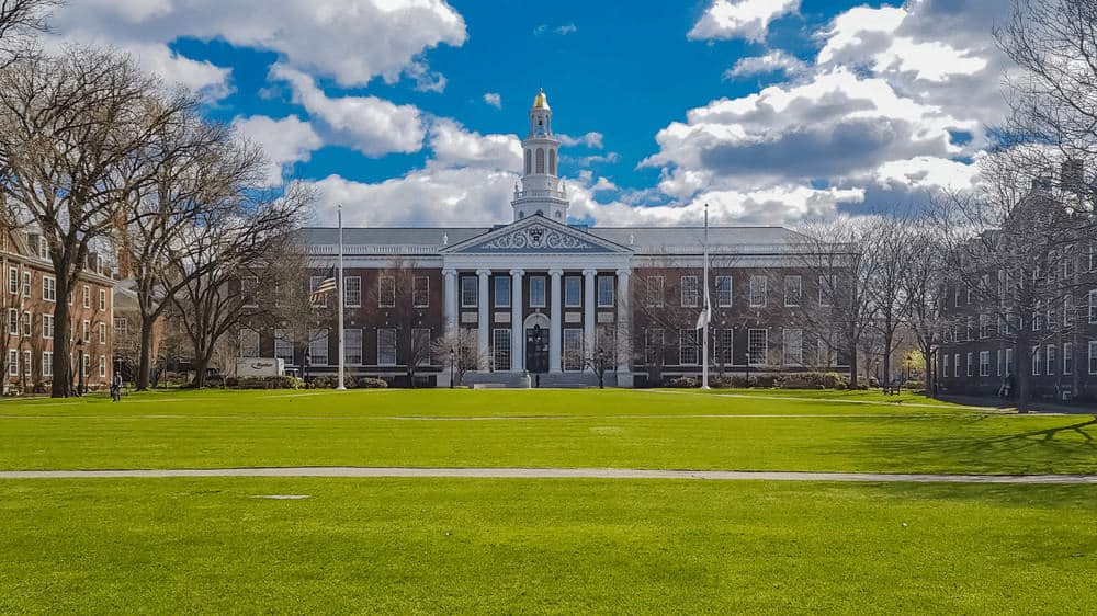 A photo of a building on the Harvard campus, surrounded by a bright blue cloudy sky and bright green grass.