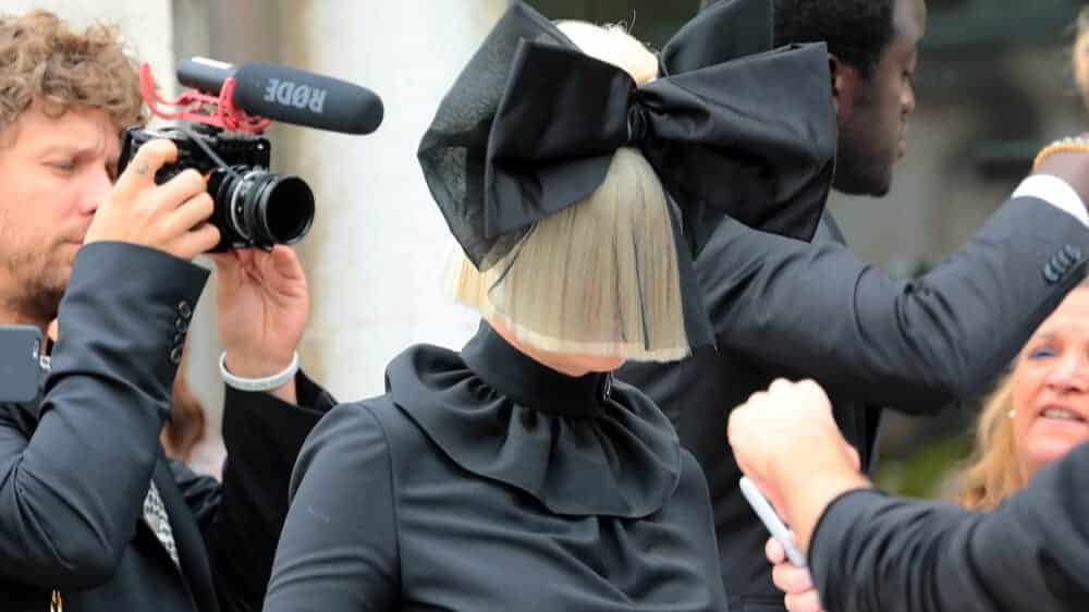 Photo of Sia in a black dress and blonde wig with a black bow.