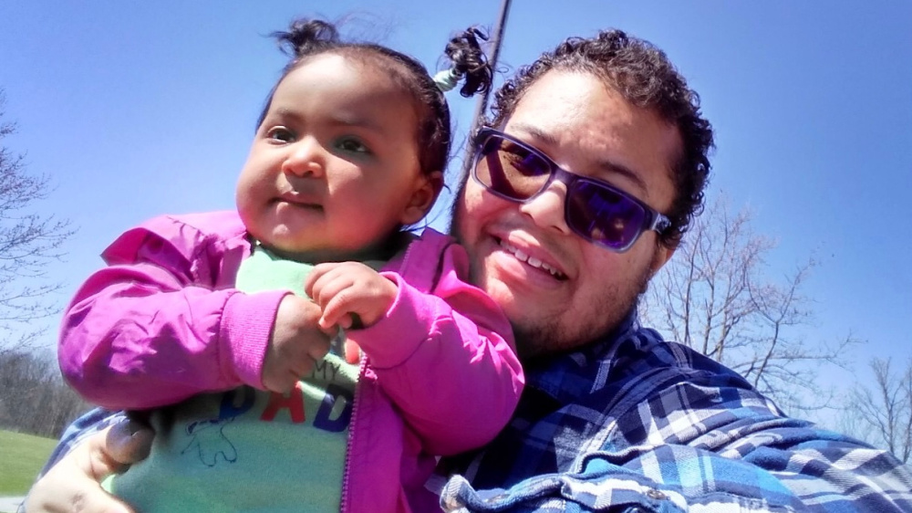 Photo of Kris and his daughter. Kris is a biracial man who has short black curly hair and tinted glasses. He is smiling while sitting holding his 11 month old daughter who has short black hair in two ponytails and is wearing a pink jacket on a sunny day at a park.