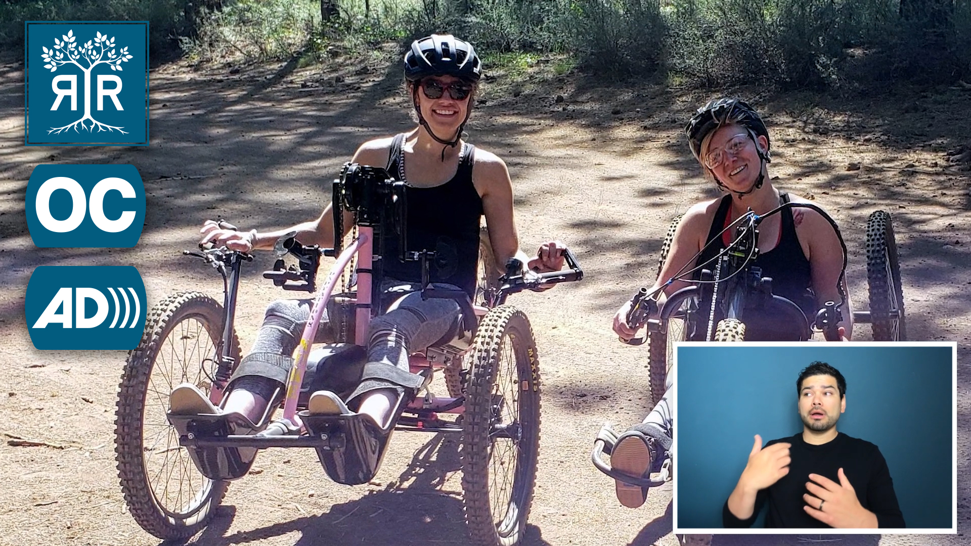 Thumbnail that shows two people smiling while seated in mountain bike hand cycles. There is an ASL interpreter in the lower right. There is the Rooted in Rights logo, an open captions icon, and an audio description icon in the upper left.