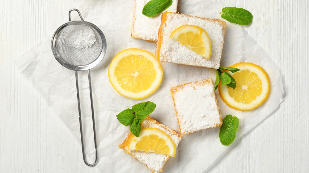Lemon bars and sieve with powdered sugar on wooden table