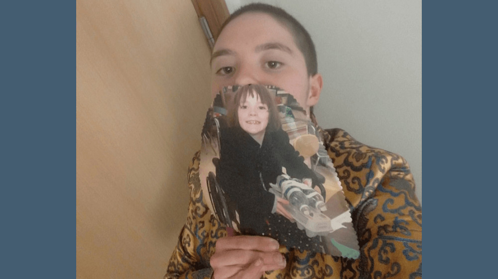 A young white woman with short hair, standing against a wall. In front of her face, she is holding a picture from when she was 8 years old, sitting in a wheelchair, smiling.