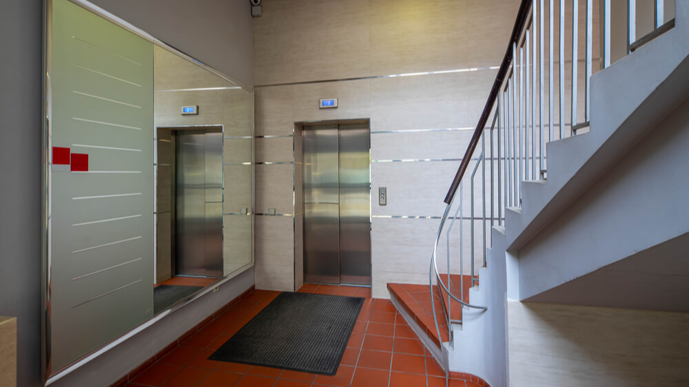 An elevator next to a staircase inside an apartment building.