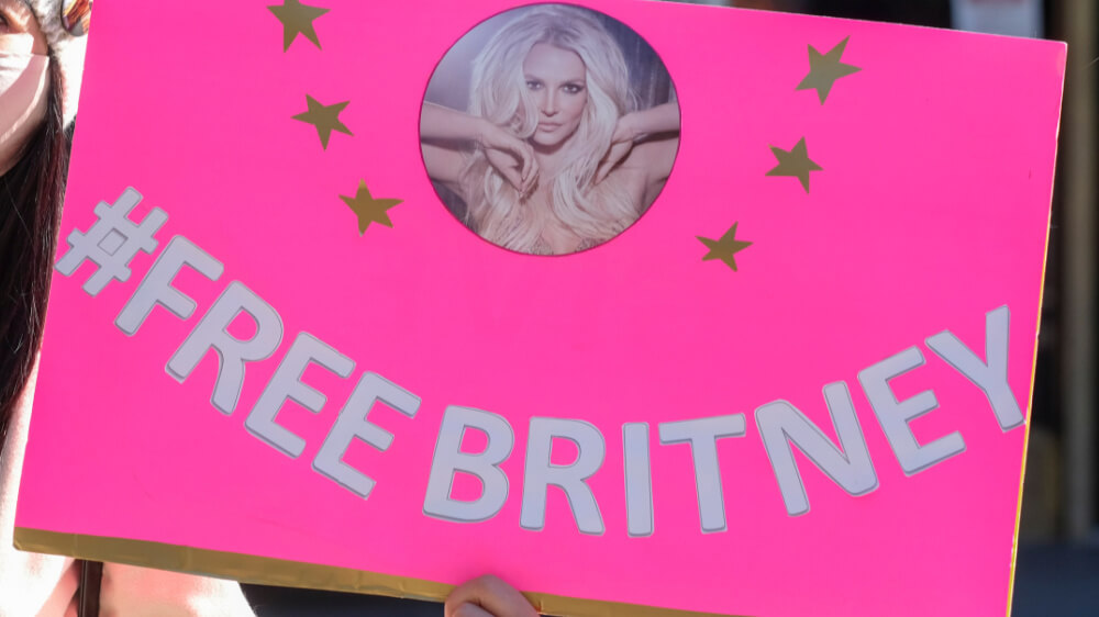 Bright pink sign with photo of Britney Spears that says #FreeBritney