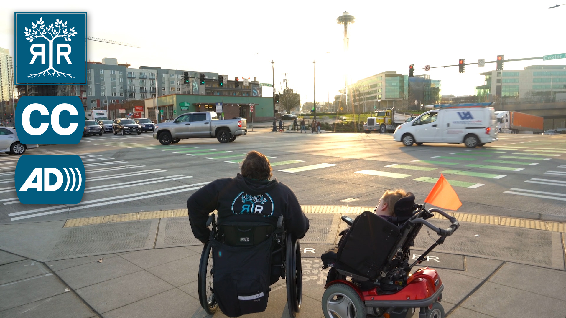 Vanessa and Clark sit in their wheelchairs on the corner of the intersection of two busy streets. There is a Rooted in Rights icon, a Closed Captioning icon, and an Audio Description icon on the left of the image.