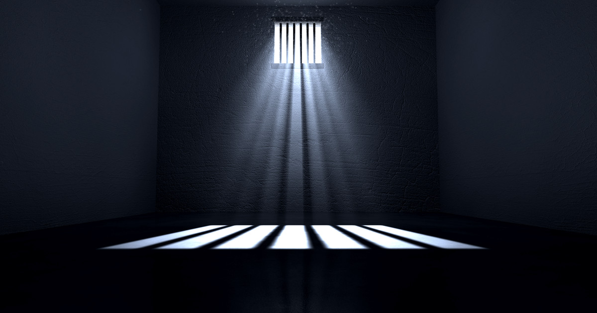 An old jail cell interior with barred up window with light rays penetrating through it reflecting the image on the floor